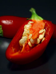 A ripe red jalapeño cut open to show the seeds