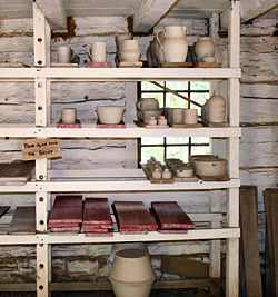 "Unfired ""green ware"" pottery on a traditional drying rack at Conner Prairie living history museum."